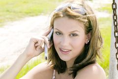 Junge blonde Frau, die auf ihrem Handy spricht Lizenzfreies Stockbild