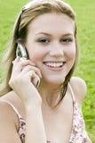 Junge blonde Frau, die auf ihrem Handy spricht Stockfotografie