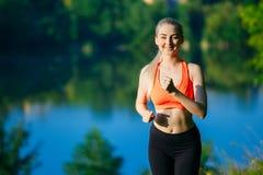 Junge blonde Frau, die auf Natur läuft Ein Sportmädchen in einem roten T-Shirt läuft entlang den Park nahe dem Fluss Stockbild