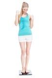 Junge blonde Frau, die auf Skalen steht Stockfoto