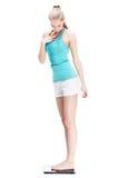 Junge blonde Frau, die auf Skalen steht Stockfotografie