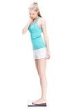 Junge blonde Frau, die auf Skalen steht Lizenzfreie Stockfotografie