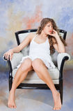 Junge blonde Frau, die auf Stuhl sitzt Lizenzfreies Stockbild