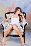 Junge blonde Frau, die auf Stuhl sitzt Lizenzfreie Stockfotografie