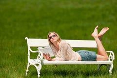Junge blonde Frau, die auf weißer Bank liegt Lizenzfreie Stockbilder