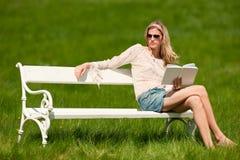 Junge blonde Frau, die auf weißer Bank mit Buch sitzt Stockfotos