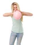 Junge blonde Frau, die Ballon aufbläst Lizenzfreies Stockfoto