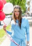 Junge blonde Frau, die bunte Ballone in der Straße hält Lizenzfreie Stockbilder