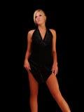Junge blonde Frau, die das Kleid zeigt Fahrwerkbeine hält Stockfotos