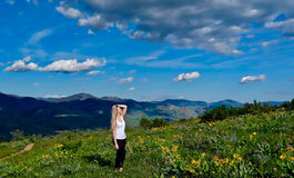 Junge blonde Frau, die in den Alpenwiesen wandert Stockfoto