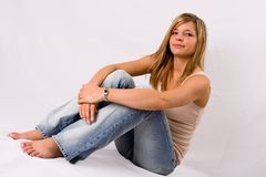 Junge blonde Frau, die in den Jeans sitzt Stockbilder