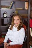 Junge blonde Frau, die in der Bibliothek sitzt Lizenzfreies Stockfoto