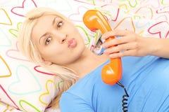Junge blonde Frau, die in der Hand im Bett mit einem Telefon und Schlag liegt Lizenzfreies Stockbild