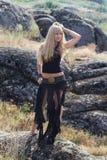 Junge blonde Frau, die in die Berge geht Lizenzfreie Stockfotos