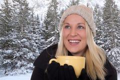 Junge blonde Frau, die draußen in der Wintertasse tee trinkt Lizenzfreies Stockfoto
