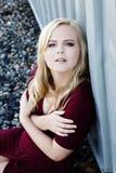 Junge blonde Frau, die draußen rotes Kleid sitzt Lizenzfreie Stockfotografie