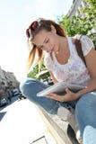 Junge blonde Frau, die draußen Tablette verwendet Stockfoto