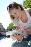 Junge blonde Frau, die draußen Tablette verwendet Stockfotografie