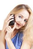 Junge blonde Frau, die durch Telefon spricht Stockbild