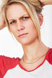 Junge blonde Frau, die durchdacht ihre Braue knittert Lizenzfreies Stockbild