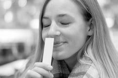 Junge blonde Frau, die ein Aroma genießt Lizenzfreie Stockfotos