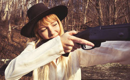 Junge blonde Frau, die ein Gewehr hält Stockfoto