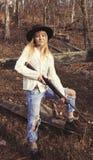 Junge blonde Frau, die ein Gewehr hält Stockbild