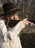 Junge blonde Frau, die ein Gewehr hält Stockfotografie