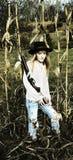 Junge blonde Frau, die ein Gewehr und eine Stellung auf einem Maisgebiet hält Lizenzfreies Stockfoto