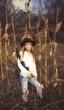 Junge blonde Frau, die ein Gewehr und eine Stellung auf einem Maisgebiet hält Lizenzfreie Stockbilder