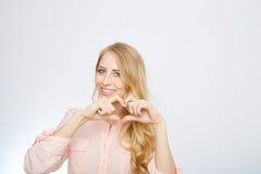 Junge blonde Frau, die ein Herzsymbol macht Stockfotografie