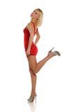 Junge blonde Frau, die ein kurzes rotes Kleid trägt Lizenzfreie Stockbilder