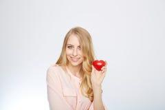 Junge blonde Frau, die ein rotes Herz hält ein getrennt worden Lizenzfreies Stockfoto