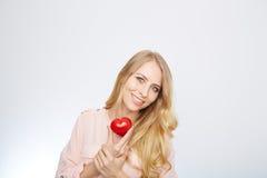 Junge blonde Frau, die ein rotes Herz hält ein getrennt worden Lizenzfreie Stockbilder
