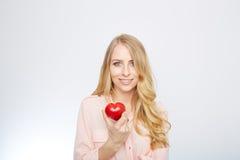 Junge blonde Frau, die ein rotes Herz hält ein getrennt worden Stockfotos
