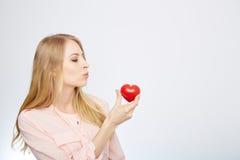 Junge blonde Frau, die ein rotes Herz hält ein getrennt worden Lizenzfreie Stockfotos