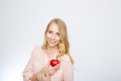 Junge blonde Frau, die ein rotes Herz hält ein getrennt worden Stockfotografie
