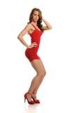Junge blonde Frau, die ein rotes Kleid trägt Stockbilder