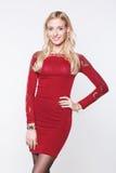 Junge blonde Frau, die ein rotes Kleid trägt Stockfotos