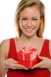 Junge blonde Frau, die ein Valentinsgrußgeschenk anhält Lizenzfreie Stockbilder