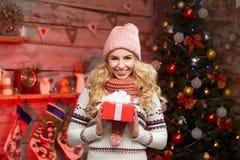 Junge blonde Frau, die eine kleine rote Geschenkbox hält Stockbilder