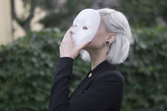 Junge blonde Frau, die eine Maske entfernt Vortäuschen, zu sein jemand anderes Konzept draußen Lizenzfreies Stockbild