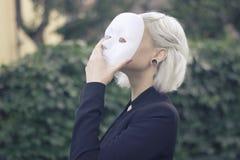 Junge blonde Frau, die eine Maske entfernt Vortäuschen, zu sein jemand anderes Konzept draußen Stockfoto