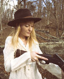 Junge blonde Frau, die eine Schrotflinte überprüft Lizenzfreie Stockfotos