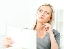 Junge blonde Frau, die eine Tablette hält Lizenzfreie Stockbilder