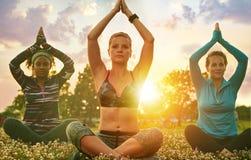 Junge blonde Frau, die eine Yogaklasse bei Sonnenuntergang im Naturpark führt Stockbild