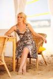Junge blonde Frau, die in einem geflochtenen Stuhl sitzt Lizenzfreies Stockbild