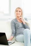 Junge blonde Frau, die an einem Laptop arbeitet Lizenzfreie Stockfotografie