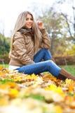 Junge blonde Frau, die in einem Park sitzt Lizenzfreie Stockfotos