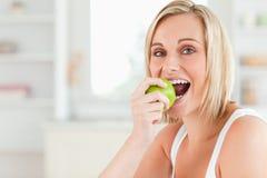 Junge blonde Frau, die einen Apfel sitzt und isst Lizenzfreies Stockfoto